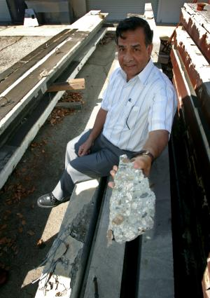 Pinaki Chakrabarti displays a section of a crushed concrete beam.