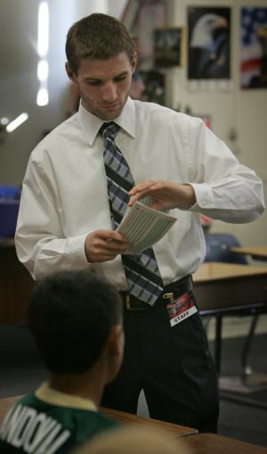 Andrew Holmes hands out test papers in a world history class