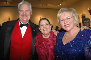 A man in a red vest and tuxedo with two women in red and blue outfits.