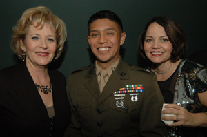 Two women stand on either side of a serviceman.