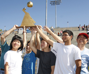 A winning team holds up their trophy.