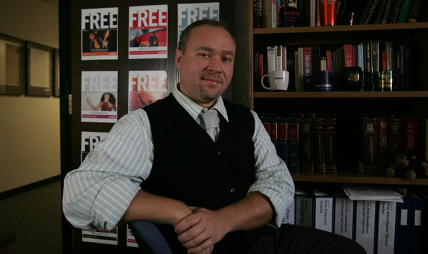 Jason Shepard stands in his office in front of a door covered with signs about freedom of the press.