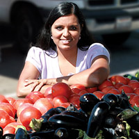 woman stands looking over a bin of tomatoes and eggplants.