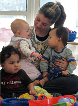 Student Leslie Ochoa cuddles with some of the infants at the Children's Center