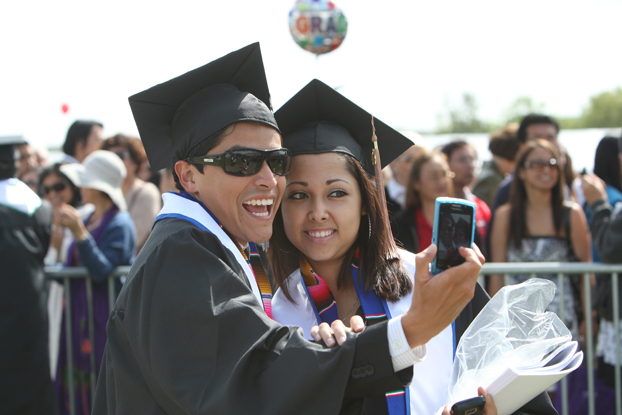 two hispanic students celebrating commencement.
