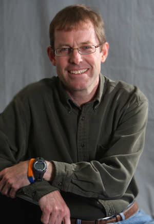 Scott Hewitt seated in front of a gray backdrop.