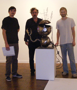 Tim Burton, center, with CSUF grads David Brokaw and Preston Daniels.
