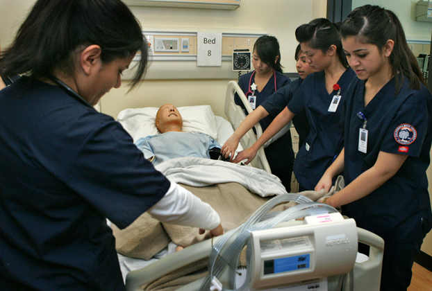 Nursing student practice over a mechanical 'patient.'
