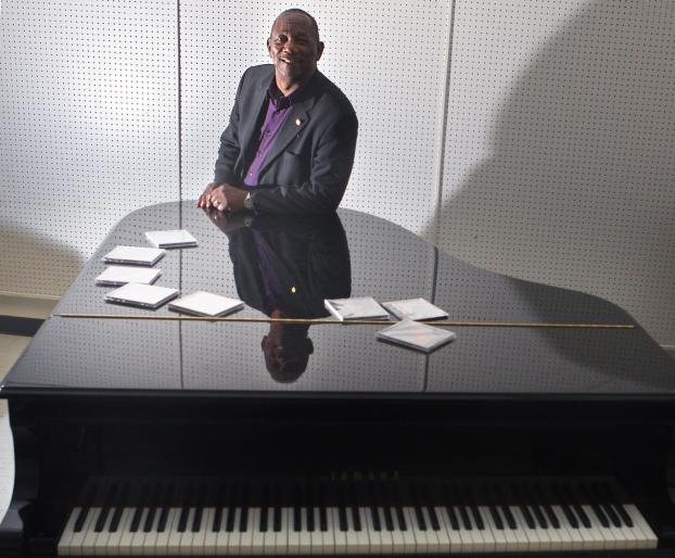 Stan L. Breckenridge poses with a piano and his CDs. Photo by Karen Tapia