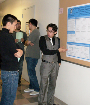 Miguel Garcia shows his poster to fellow HHMI participants.