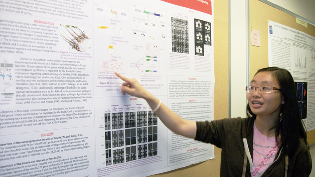 Tran Trinh points to the poster on her summer research.