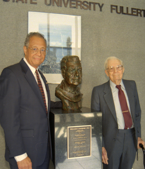 Presidents Gordon and Langsdorf stand on either side of bronze bust of Langsdorf which graces the entrance of Langsdorf Hall.