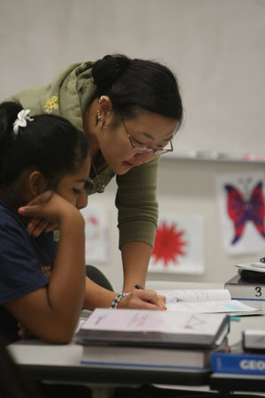 Candice Harrington stands next to one of the Project MISS students guiding her on a math problem.