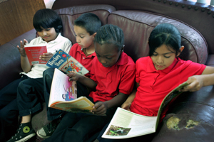 Youngsters sit on a sofa reading.