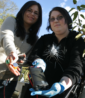 Two female students display the sensors used in a plant hydraulic study.