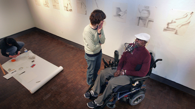 Man in wheelchair talks to a woman standing next to him.