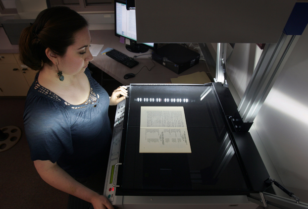 Dani Stephan uses a scanner to digitize a course catalogue.