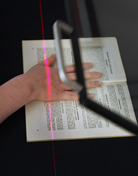 Close up of Dani Stephan's hand placing a catalog in the scanner.