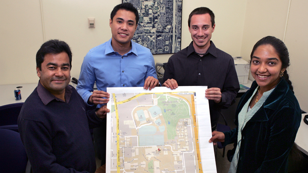 three students and thier professor hold a copy of a Google map of the campus.
