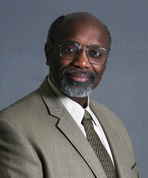 Portrait photo showing black man wearing a light beige suit and glasses.