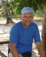 Brady Rhodes wearing a blue cap and t-shirt on a beach in Thailand.
