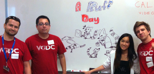 "Four students stand before a white board with drawings from the game ""A Ruff Day"""