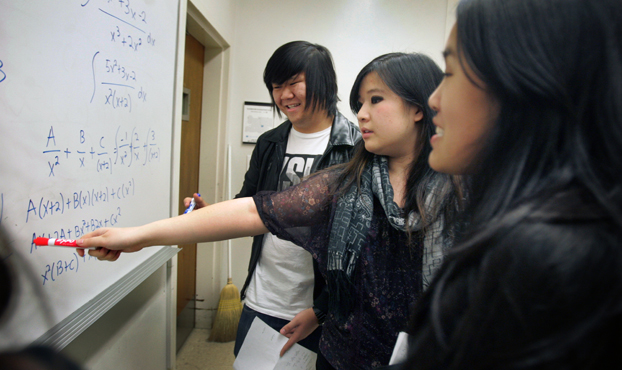 Three students look at a white board covered with mathematical problems.