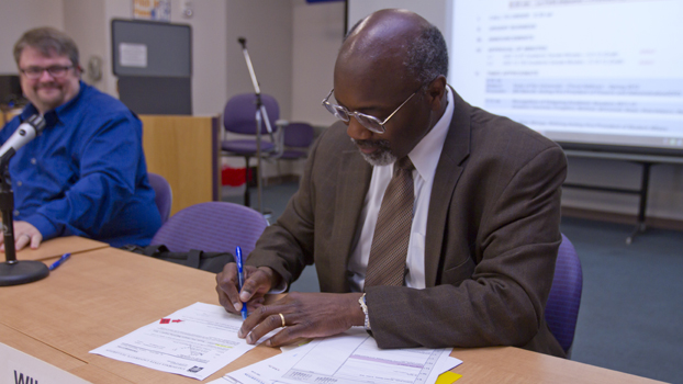 Black man in a business suit signs a document.