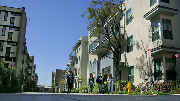 students walk by some of the latest student housing.