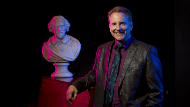 Jim Volz, in black suit and fushia shirt, stands beside an upright piano and a bust of William Shakespeare.