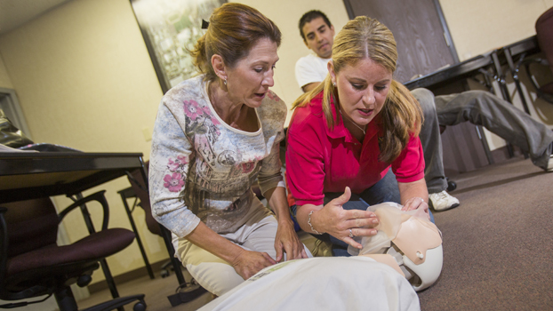 Two women work with a CPR training mannikin