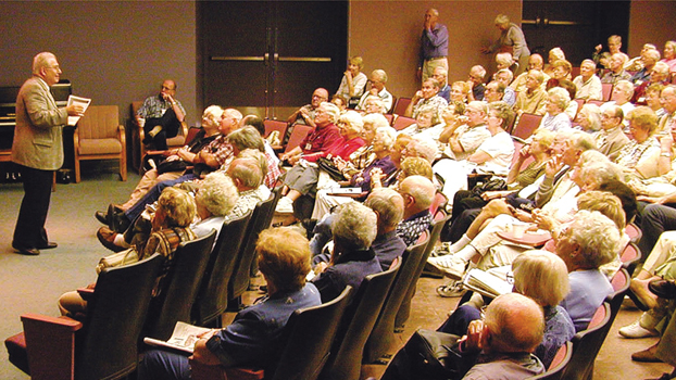 Older gentleman gives lecture in auditorium
