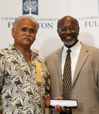two men stand in front of a backdrop that reads Cal State Fullerton