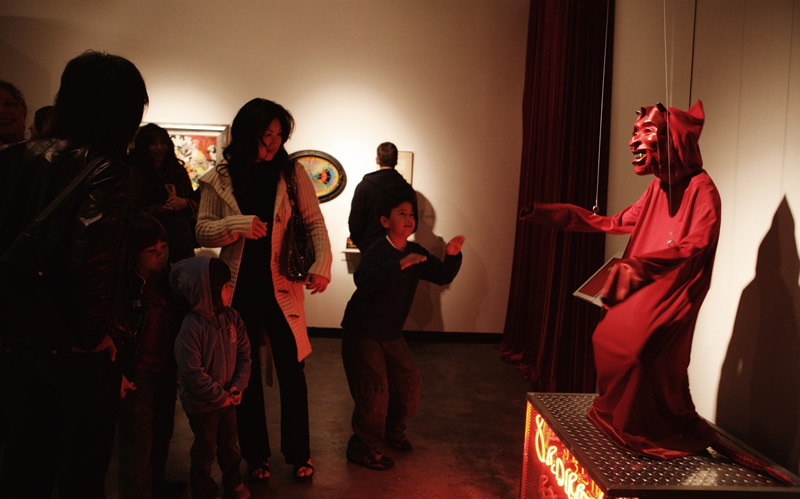 Grand Center Art Center visitors looking at a large hooded dancing devil marionette