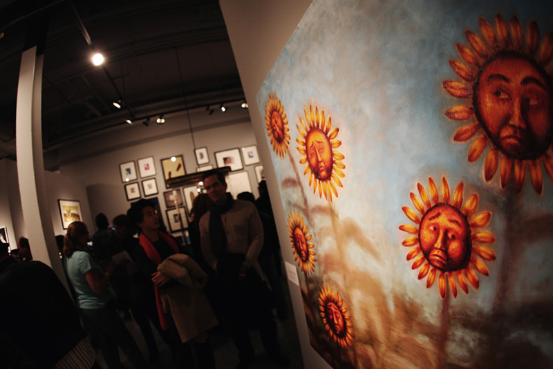 Grand Center Art Center visitors looking at a painting of sunflowers