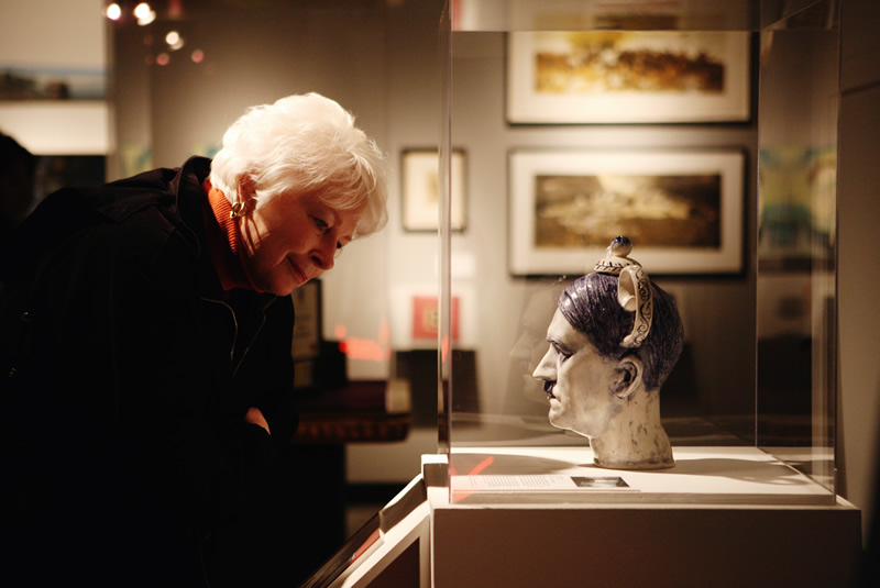 Grand Center Art Center visitor looks at a sculpture of a teapot shaped in the form of Adolf Hitler's head